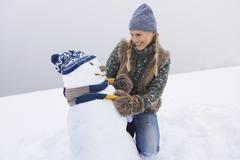 Stock Photo of Happy Young Woman Dressing Snowman