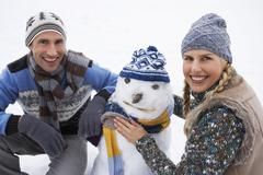 Happy Young Couple Dressing Snowman Stock Photos