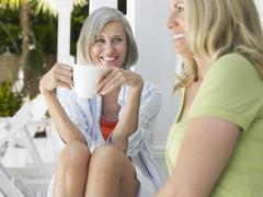Happy Middle Aged Women Sitting On Verandah - stock photo