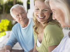 Three Happy Mature People Sitting On Verandah Stock Photos