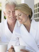 Stock Photo of Couple In Bathrobes With Cups On Verandah