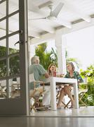 Middle Aged People Sitting At Verandah Table - stock photo