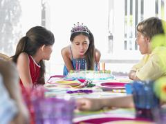Girl Blowing Birthday Candles At Party Stock Photos