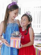 Two Happy Girls In Tiaras Holding Present - stock photo