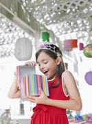 Cheerful Girl Opening Birthday Present At Party Stock Photos