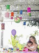 Mother With Sleeping Daughter At Birthday Table Stock Photos