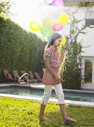 Girl Walking With Balloons By Swimming Pool - stock photo