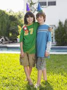Portrait Of Two Boys In Party Hats On Lawn - stock photo