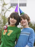 Portrait Of Two Boys In Party Hats Outdoors Stock Photos