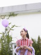 Girl In Tiara And Feather Boa Holding Balloon Stock Photos
