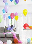 Stock Photo of Girl In Fairy Wings With Balloons On Sofa