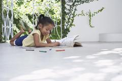 Girl Drawing With Crayons While Lying On Porch - stock photo