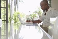 Man Using Laptop At Dining Table - stock photo