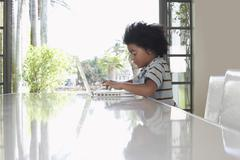 Boy Using Laptop At Dining Table Stock Photos