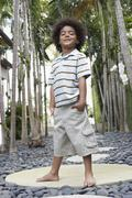 Little Boy With Hands In Pockets On Stepping Stone - stock photo