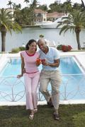 Couple Holding Cocktails While Leaning On Pool Banister - stock photo