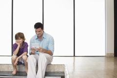 Father Playing Handheld Video Game Sitting Next To Son At Home Stock Photos