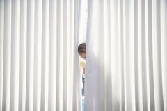 Girl Peeking From Curtains At Home - stock photo