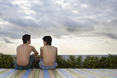 Teenage Friends Sitting On Deck Overlooking Ocean Stock Photos