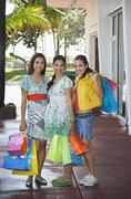 Teenage Girls Carrying Shopping Bags On Sidewalk - stock photo