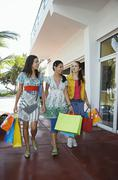 Teenage Girls With Shopping Bags Walking On Pavement - stock photo