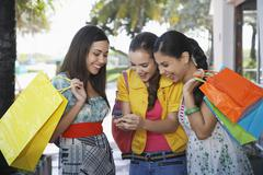Teenage Girls With Shopping Bags Text Messaging Stock Photos
