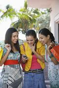 Teenage Girls With Shopping Bags Text Messaging - stock photo