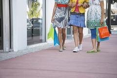 Teenage Girls With Shopping Bags Walking On Pavement Stock Photos