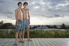 Teenage Friends Standing On Deck Overlooking Ocean Stock Photos