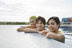 Teenage Friends Resting At The Edge Of Swimming Pool - stock photo