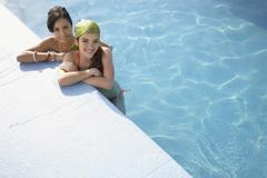 Teenage Girls Relaxing At The Edge Of Swimming Pool - stock photo