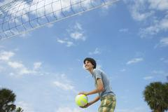 Teenage Boy Playing Beach Volleyball - stock photo