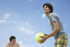 Teenage Boys Playing Beach Volleyball - stock photo