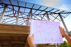 architecture drawings in hand on house building - stock photo