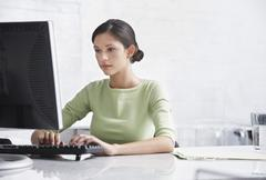 Businesswoman Using Computer At Desk - stock photo