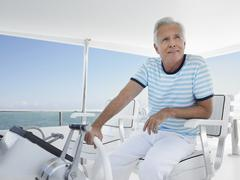 Man At The Helm Of Luxury Yacht - stock photo