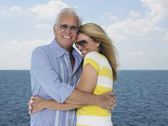 Stock Photo of Couple Embracing With Ocean In Background