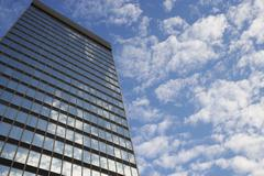 Sky and clouds reflecting in skyscraper windows low angle view Stock Photos