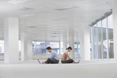 Business People Using Laptops In Empty Office Space Stock Photos
