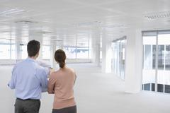 Business People Looking At Plan And Empty Office Space - stock photo