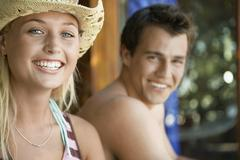 Stock Photo of Woman In Sunhat Sitting Beside Boyfriend