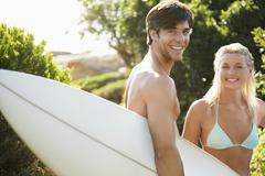 Happy Couple With Surfboard At Beach - stock photo