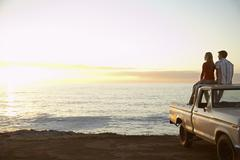 Couple On Pick-Up Truck Parked In Front Of Ocean - stock photo