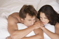 Couple Lying In Bed Looking Away - stock photo