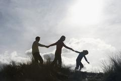Family Holding Hands While Walking On Beach - stock photo