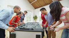 Happy group of friends hanging out together and playing a game of table football Stock Footage