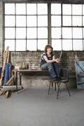Thoughtful Female Artist In Workshop - stock photo