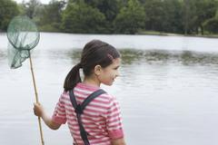 Girl Holding Fishing Net By Lake - stock photo