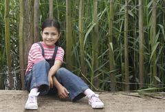 Girl Sitting In Front Of Fence - stock photo