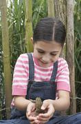 Girl Playing With Frog Stock Photos